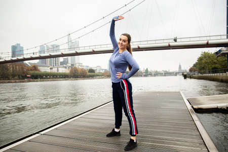 Sporty young woman in in sportswear doing stretching exercises on a wooden pier near the river. Behind the panorama of the big city. Active lifestyle. 版權商用圖片