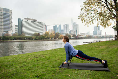 Young athlete woman doing a push up with push-up bars on the grass, near the river, on the background of the city. Sport and training concepts.