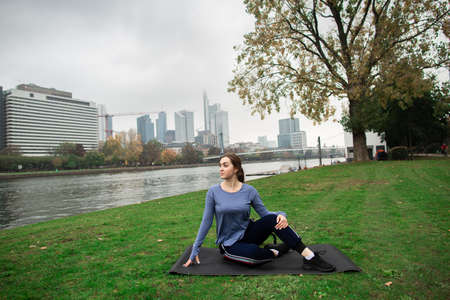 Young athlete woman doing exercises lying on the grass near the river, against city background.