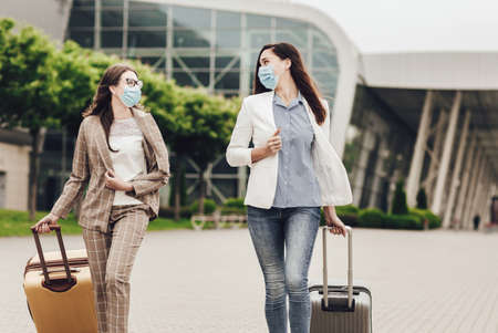 Two business women in protective masks with suitcases near the airport. Business trips during coronavirus quarantine