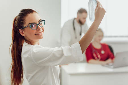 Young female doctor in hospital looking at x-ray. The other two doctors communicate in the background. Medicine and treatment concept