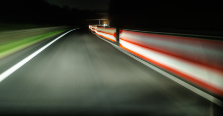 View from a moving car on the highway on one lane, on a renovated road. Safety barriers are visible from the side