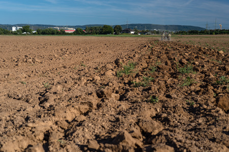 The tractor pulls the plow and plowed field on a sunny summer day.