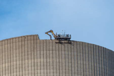 Demolition of the atomic chimney. Remote controlled excavator with shears works from above. Stock Photo