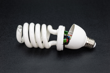 Broken energy saving light bulb, isolated on a black background. Standard-Bild - 115081016