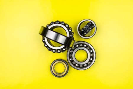 Ball bearing lying on a yellow background with copy space on the sides. Flat view from above.