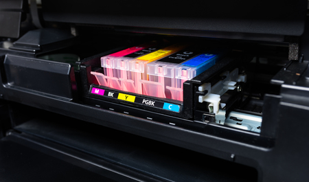 Close-up shot of a CMYK ink cartridges in a color printer.