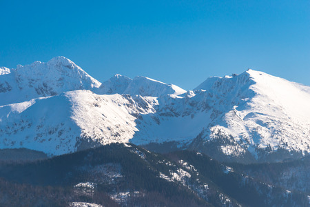 A beautiful view of the Polish Tatra Mountains. Sunny, beautiful day in the winter, snow-capped mountains and blue sky.