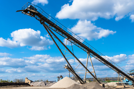 Conveyor over heaps of gravel on an industrial cement plant.