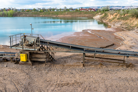 A string of transport in a gravel pit for transporting gravel and sand over the distances, belts go along the lake. Stock Photo