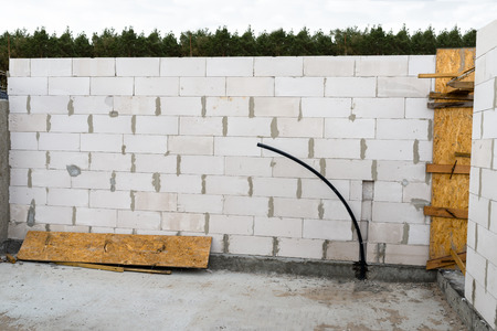 The walls of the house are built with white stones and are in the form of ribbed stones, wooden formwork.