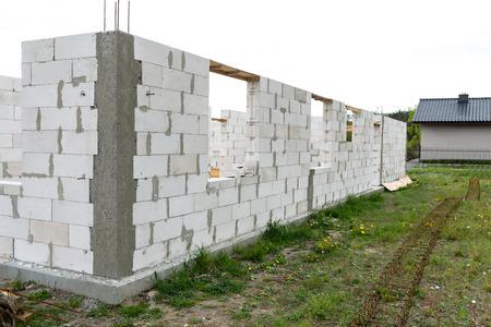 De muren van het huis zijn gebouwd met witte stenen en zijn in de vorm van geribbelde stenen, houten bekisting.