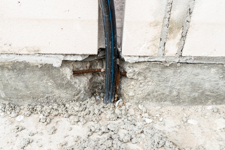 An electric high voltage cable protruding from the foundation of the house being built.