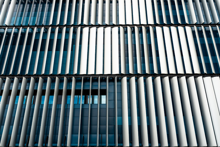 The facade of a modern building with an innovative facade made of automatic, movable blinds.