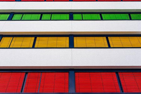 Elevation of a modern office building with different colors of blinds on each floor.