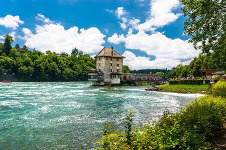 Neuhausen am Rheinfall, Switzerland - 23 July 2019. Waterfall on the river Rhine in Neuhausen am Rheinfall, in Switzerland. Visible old castle on a small island, which is now a restaurant. 에디토리얼