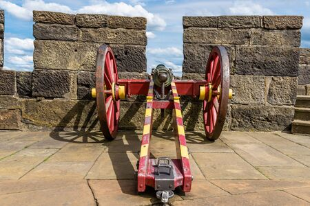 An antique cannon in a red-yellow color on the walls of a medieval castle. Stock Photo