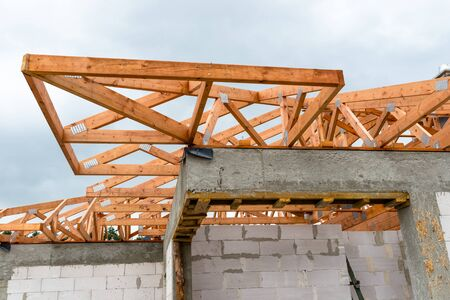 Roof trusses not covered with ceramic tile on a detached house under construction, visible roof elements, battens, counter battens, rafters. Archivio Fotografico