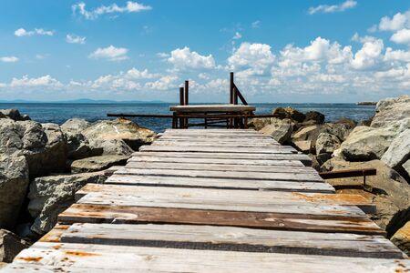 Stary, drewniany pomost nad pięknym Morzem Czarnym w Bułgarii, stojący na kamienistym brzegu, w tle niebo z chmurami.