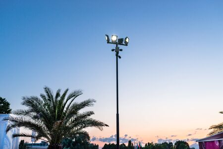 Mast at the beach with four spotlights and four cameras attached.