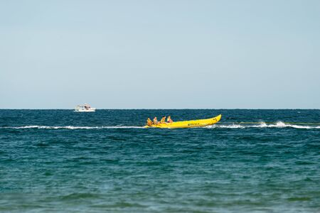 Sunny Beach, Bulgaria July 13, 2019. Inflatable recreational banana boat with people towed by a motorboat in the Black Sea on the shores of Sunny Beach in Bulgaria.