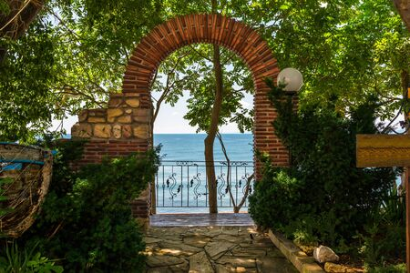 A brick wicket with an arch at the top behind which you can see the beautiful Black Sea at the Nessebar coast in Bulgaria.