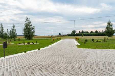 Entry for cars into the property made of openwork concrete pavement filled with colorful pebbles, around is green grass and small trees. Фото со стока