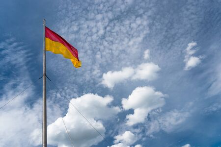 Flag in red at the top and yellow at the bottom, hanging on the mast, waving in the wind. In the background a blue sky with white clouds.