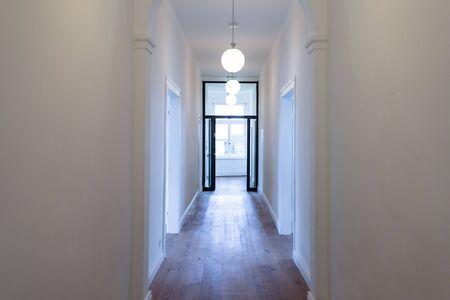 Un grand hall dans une pièce haute aux murs blancs, trois lustres visibles et une porte vitrée ouverte au fond du couloir éclairée par la lumière de la fenêtre.