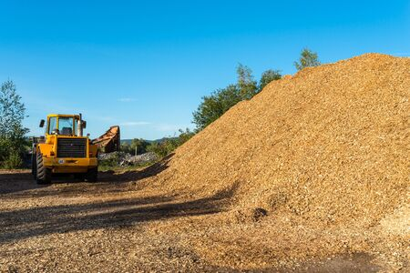 A large pile of wood chips lying on a square, with a blue sky in the background, visible bulldozer. Reklamní fotografie