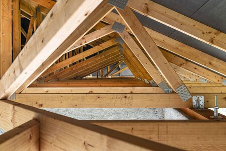 Roof trusses covered with a membrane on a detached house under construction, view from the inside, visible roof elements and truss plates.