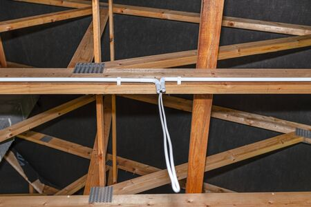 Lighting cables in plastic wiring pipes in a newly built house mounted on roof trusses.