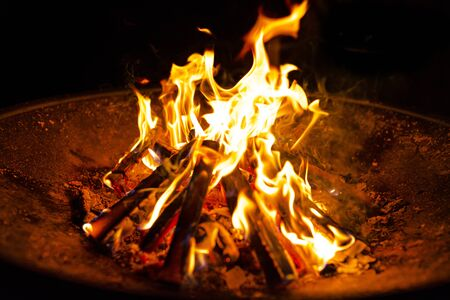 High flames from a burning wood fire on a metal grate at night.