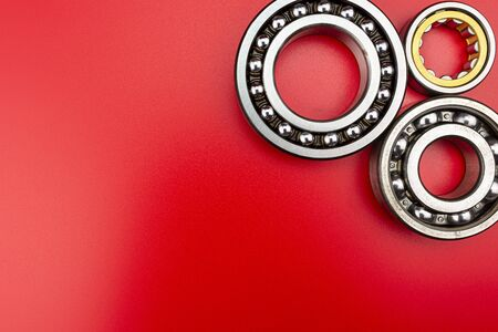 Ball bearing lying on a red background with copy space on the left side. Flat view from above.