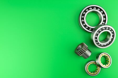 Ball bearing lying on a green background with copy space on the left side. Flat view from above.