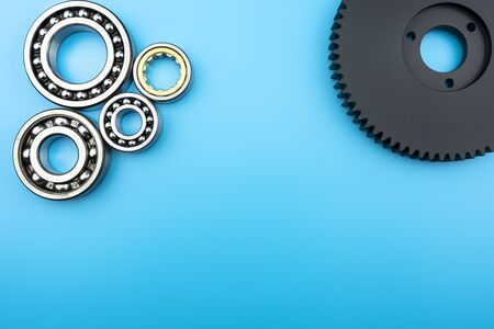 Ball bearing and black and white plastic gear lying on a blue background with copy space in the middle. Flat view from above.