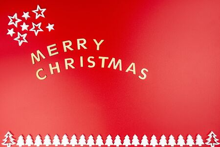 The Inscription Merry Christmas made of wooden letters, lying flat from above, isolated on a red background. White wooden Christmas trees arranged in a row at the bottom.