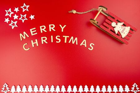 The Inscription Merry Christmas made of wooden letters, lying flat from above, isolated on a red background. White wooden Christmas trees arranged in a row at the bottom and wooden sleds.