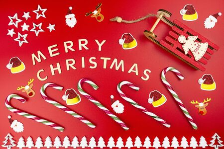 The Inscription Merry Christmas made of wooden letters, lying flat from above, isolated on a red background. Visible candy canes, wooden Christmas trees, sleds and golden reindeers.