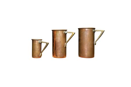 Vintage, two large and one small cup for drinks made of copper and brass, isolated on a white background Stock Photo