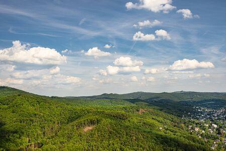 Paesaggio di foresta verde sulle colline in estate con cielo azzurro e nuvole bianche. Foto scattata in Germania Ovest. Archivio Fotografico