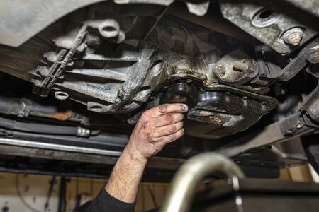 The car mechanic bolts a new screw with a copper washer to the oil sump, in a diesel engine.