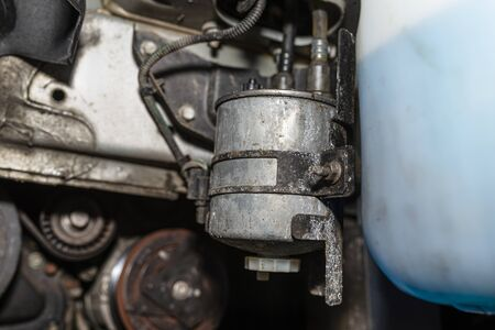 Worn fuel filter mounted and screwed on the car in the wheel arch. Stock Photo