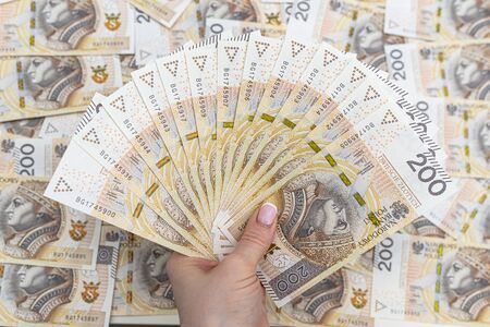 The woman is holding Polish banknotes on the front side, face value 200 PLN arranged in a fan, in the background a pile of Polish banknotes. Reklamní fotografie