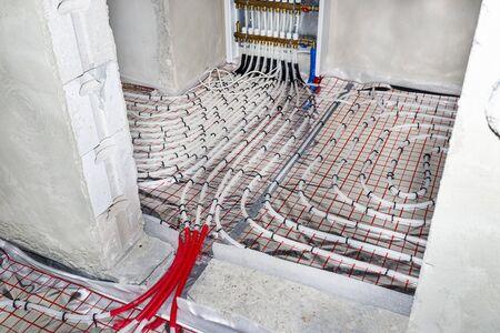 Weiße Rohre von Fußbodenheizungen, die in einem Einfamilienhaus auf einer Isolierfolie angeordnet sind und durch das Fundament des Hauses in der Tür führen.