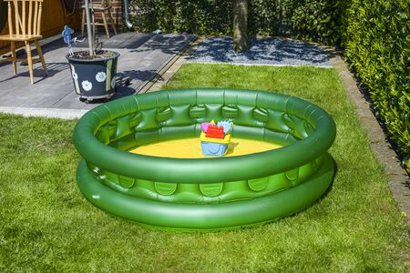 A small family pool for children in green color, placed on the grass in the garden. Banque d'images
