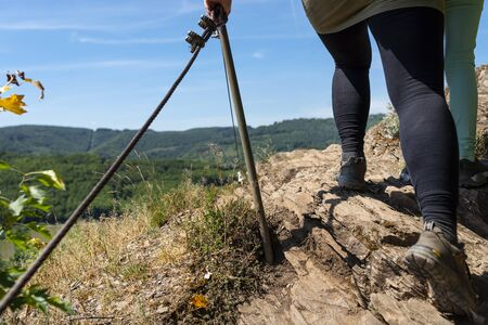 A woman walking a trail through the vineyards on a rocky, slate surface in specialized climbing shoes by a metal railing. Stock Photo