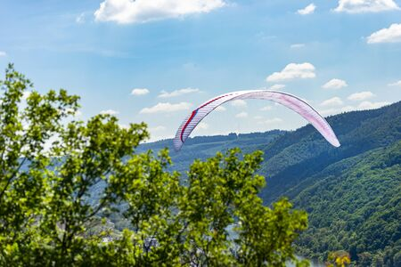 A man flying a white paraglider over the forest and the river on a beautiful sunny day. Stock Photo
