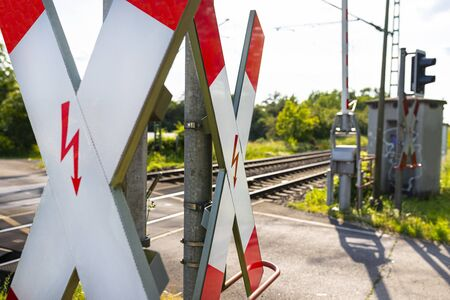 Guarded railroad crossing in the countryside with open barriers and cross of Saint Andrew. Stock Photo