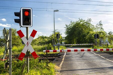 Guarded railroad crossing with closed barriers, red warning light and cross of Saint Andrew. Stock Photo